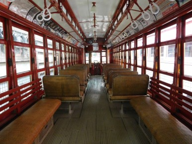 This trolley has rattan seats and overhead hangers for standing passengers to hold on to.