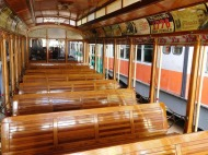 This trolley has all forward-facing bench seats and open sides.