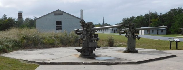 Behind these two 3-inch guns are barracks and other buildings. One of the park's several World War II observation towers stands to the left.