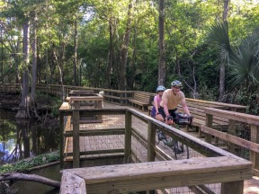 Tad and Lea ride their tandem up the Prairie Creek Boardwalk along the Gainesville-Hawthorne State Trail.