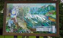 This stained glass mosaic depicting Star City's riverfront history, which included glassmaking, stands in a local park.